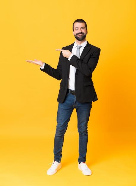 Het schot van gemiddelde lengte van de bedrijfsmens over geïsoleerde gele holding copyspace denkbeeldig op de palm om een advertentie op te nemen Premium Foto