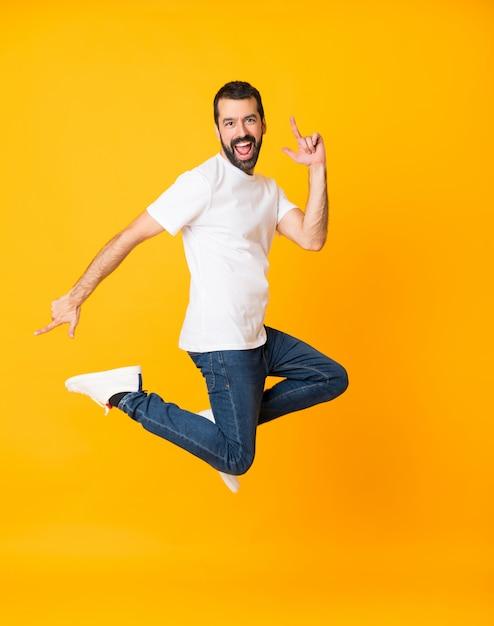 Het schot van gemiddelde lengte van de mens met baard die over geïsoleerde gele achtergrond springen Premium Foto