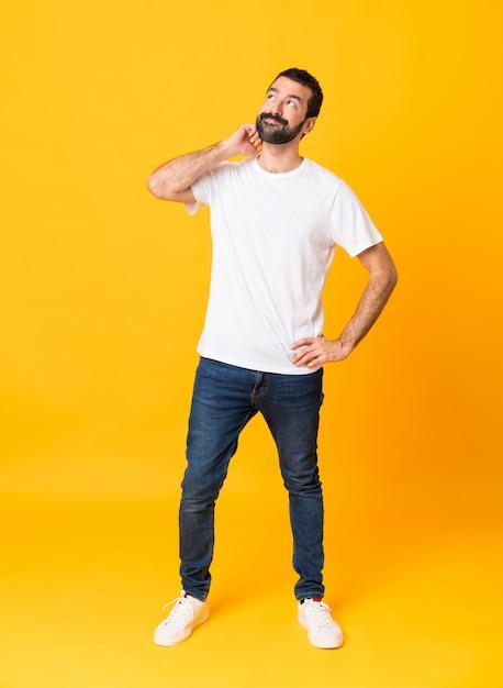 Het schot van gemiddelde lengte van de mens met baard over geïsoleerd geel denkend een idee Premium Foto