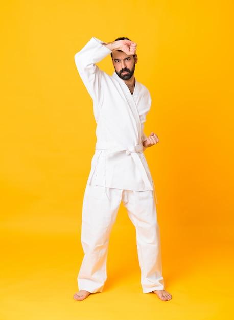 Het schot van gemiddelde lengte van de mens over geïsoleerde gele het doen karate Premium Foto