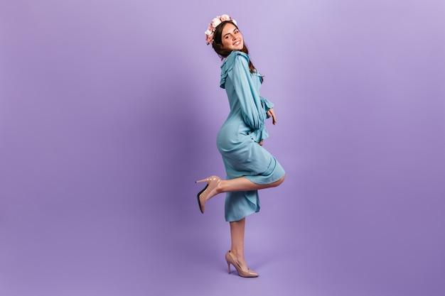 Het schot van gemiddelde lengte van positieve jonge brunette in hielen en midikleding. vrouwelijk model met bloemen in haar haar lachend op lila muur. Gratis Foto