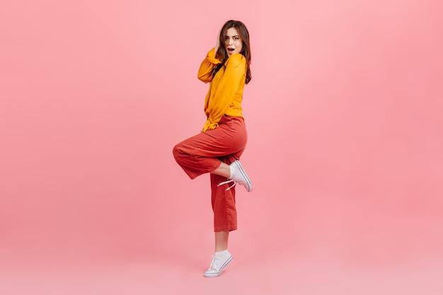 Het schot van gemiddelde lengte van verbaasde brunette op roze muur. vrouw in lichte blouse en broek hief koket haar been op. Gratis Foto