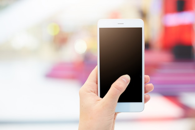 Het schot van onherkenbare vrouw houdt moderne slimme telefoon met het lege exemplaar zwarte scherm Gratis Foto