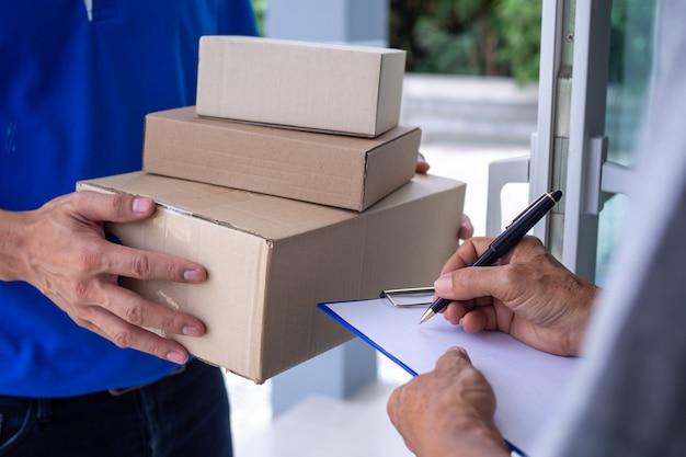 Het shoppermeisje tekent op het klembord om de pakketdoos van de bezorger te ontvangen. snelle bezorgservice Premium Foto