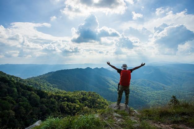 Het silhouet van de mens steunt handen op de piek van berg, succesconcept Premium Foto