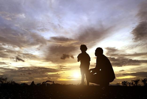 Het silhouet van de vader en zoon die genoten van de zonsondergang voor het concept vaderdag liefde-vakantie Premium Foto