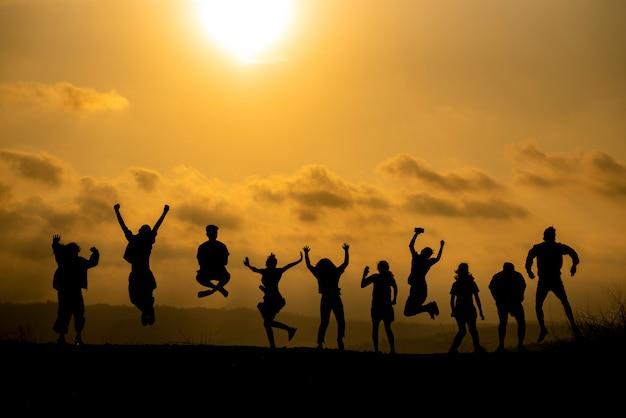 Het silhouet van een groep mensen viert succes op de heuveltop. Premium Foto