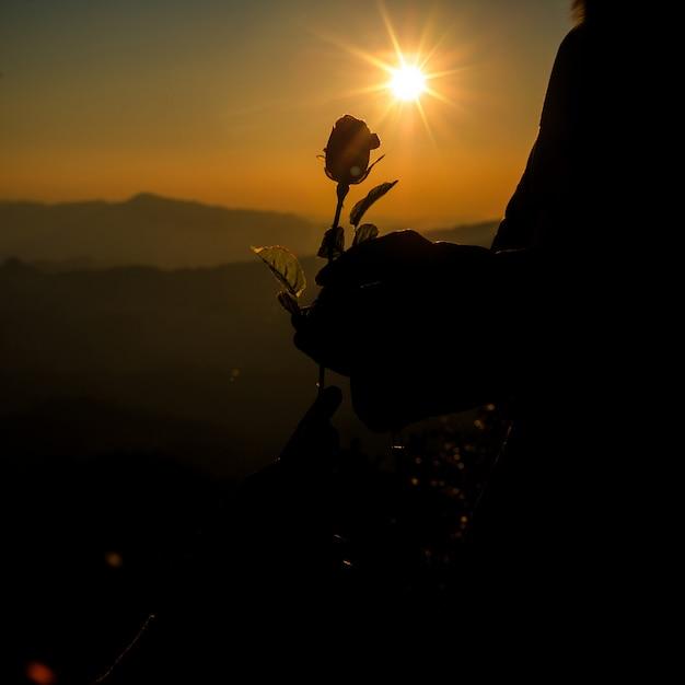 Het silhouet van paarholding nam op heuvel toe in de horizon van de zonsondergangtijd op achtergrond Gratis Foto