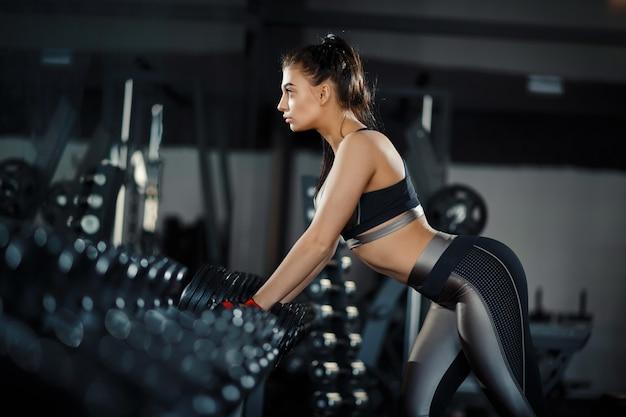 Het slanke, bodybuildermeisje, heft zware domoor op die zich voor de spiegel bevindt terwijl in de gymnastiek opleidt. sportconcept, vetverbranding en een gezonde levensstijl Premium Foto