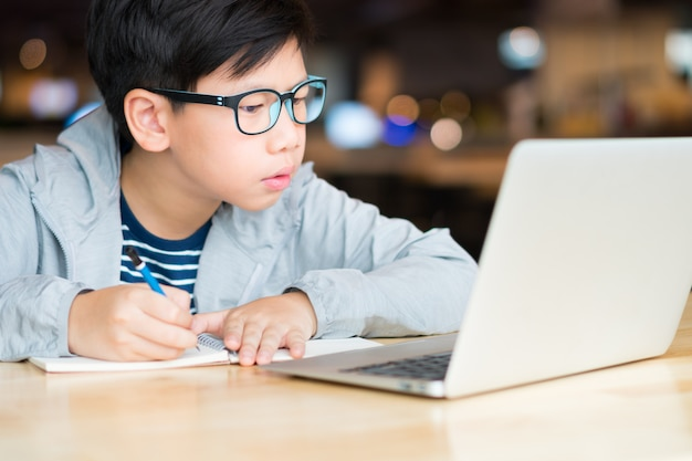 Het slimme kijken aziatische preteen jongen die en computerlaptop schrijven met behulp van die online lessen bestuderen. onderzoeken, bestuderen en oplossen van probleem met concentratie. online leren en zelfstudie concept. Premium Foto