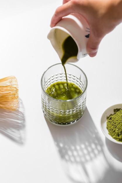 Het smakelijke matcha-thee gieten in een glas Gratis Foto