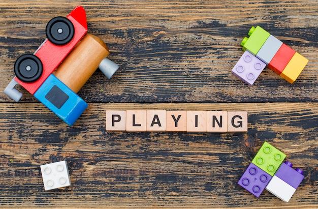 Het speelspeelgoedconcept met houten kubussen, jong geitjespeelgoed op houten vlakte als achtergrond lag. Gratis Foto