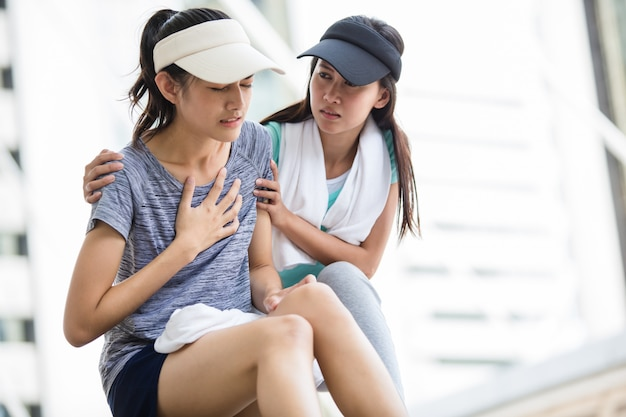 Het sportmeisje probeert om haar vriend te helpen die het hebben van een hartzeer terwijl het aanstoten in de stad. Premium Foto