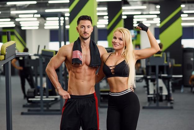 Het sportpaar stelt in de gymnastiek na een training. een jonge man omhelsde zijn vriendin in de taille. Premium Foto