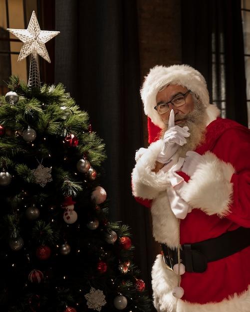 Het stellen van de kerstman naast kerstmisboom Gratis Foto