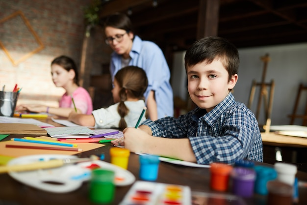 Het stellen van little boy in art class Premium Foto