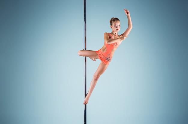 Het sterke en sierlijke jonge meisje dat acrobatische oefeningen op een pyloon uitvoert Gratis Foto
