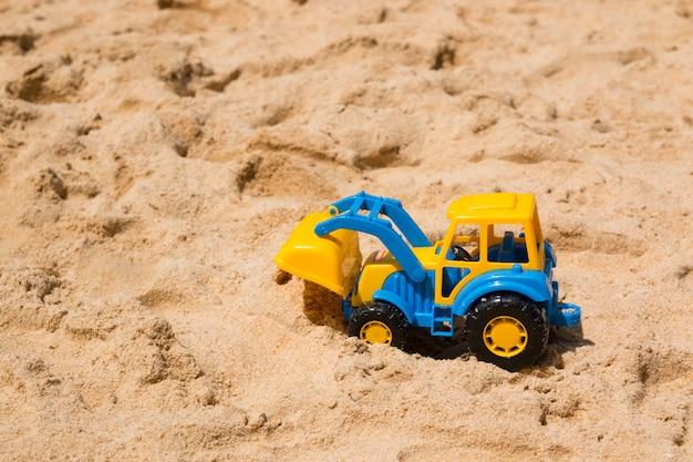 Het stuk speelgoed van kinderen graafwerktuig in het zand Premium Foto