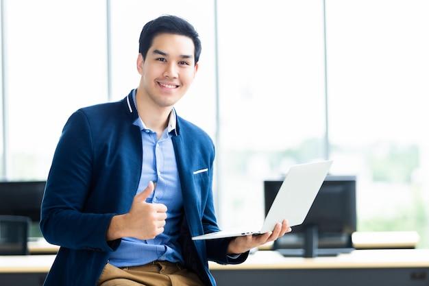 Het succesvolle jonge aziatische zakenman tonen beduimelt omhoog Premium Foto