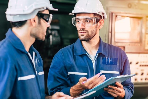 Het teamwerk van de ingenieur werkt met arbeider samen om fabrieksmachine te controleren Premium Foto