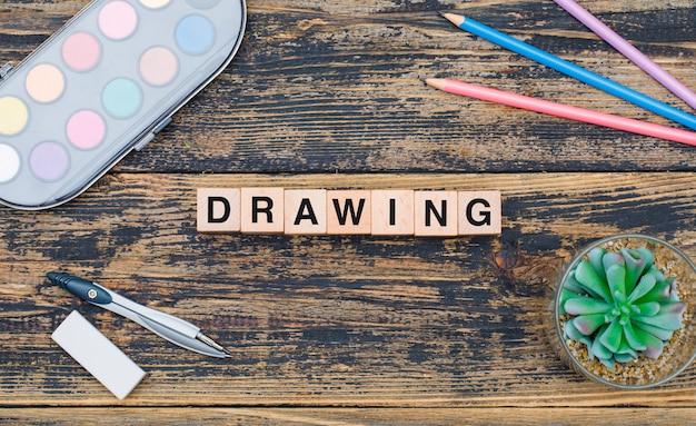 Het tekeningsconcept met houten kubussen, installatie, schoollevering op houten vlakte als achtergrond lag. Gratis Foto
