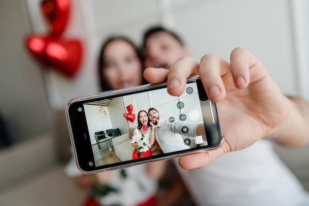 Het telefoonscherm met selfie van man en vrouw in de telefoonzitting van de liefdeholding op laag thuis Premium Foto