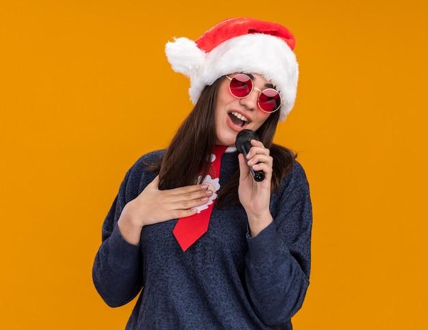 Het tevreden jonge kaukasische meisje in zonnebril met santahoed en santastropdas legt hand op borst en houdt mic die beweert te zingen te zingen Gratis Foto
