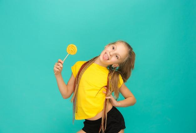 Het tienermeisje met kleurrijke lolly op een blauwe muur Gratis Foto