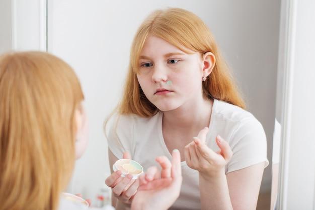 Het tienermeisje onderzoekt acne voor spiegel Premium Foto