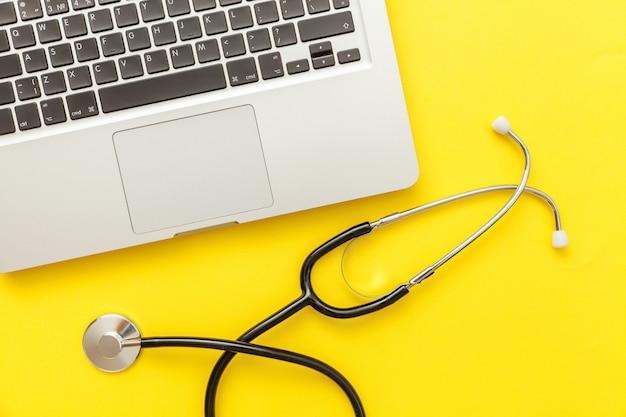 Het toetsenbordlaptop van de stethoscoop die op geel wordt geïsoleerd Premium Foto