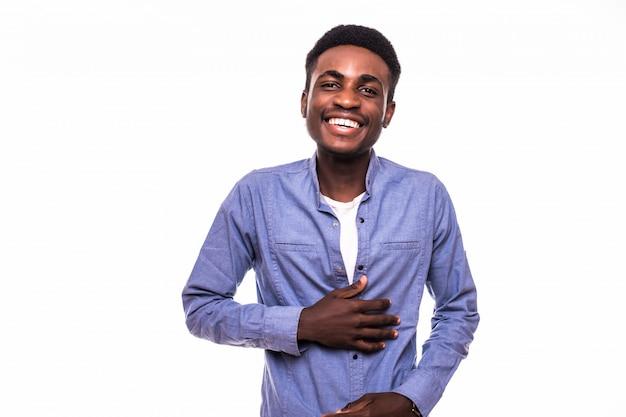 Het toevallige jonge afrikaanse mens stellen voor camera die op witte muur wordt geïsoleerd Gratis Foto
