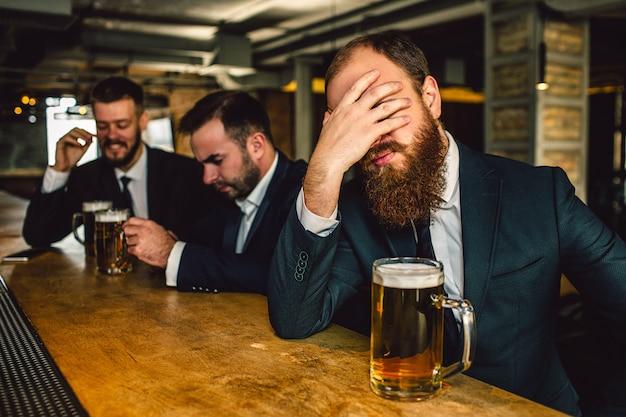Het uitgeputte en droevige gezicht van de jonge bebaarde mandekking met hand. hij zit aan de bar. bierpul is er. andere twee mannen zitten achter. Premium Foto
