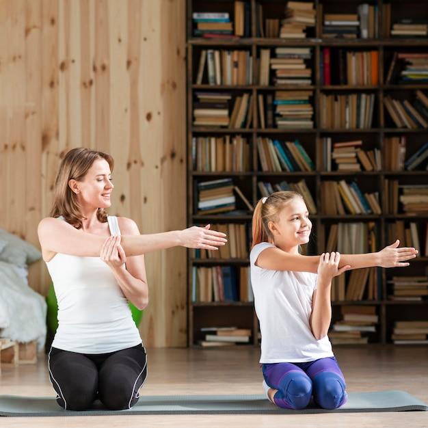 Het uitrekken van de moeder en van de dochter wapens op yogamat Gratis Foto