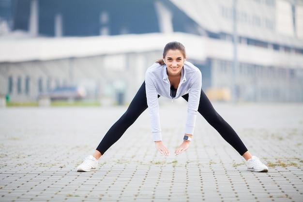 Het uitrekkende lichaam van de vrouw, die oefeningen op straat doet Premium Foto