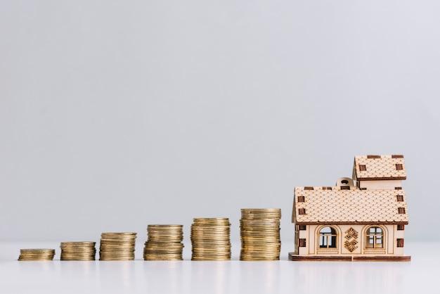 Het vergroten van gestapelde munten dichtbij huismodel Gratis Foto