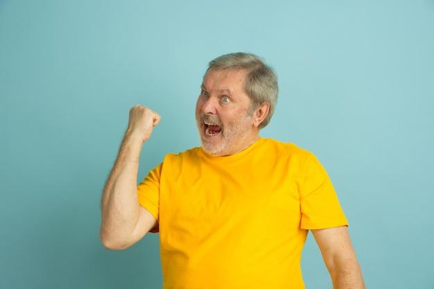 Het vieren van winnen, sport. blanke man portret geïsoleerd op blauwe studio achtergrond. mooi mannelijk model in geel overhemd poseren. Gratis Foto