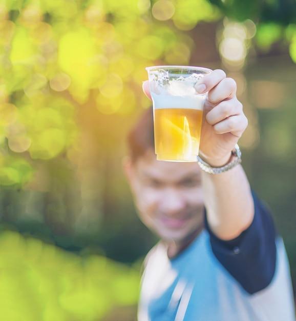 Het vieringsbier juicht concept toe - sluit omhoog hand steunend glazen bier Gratis Foto