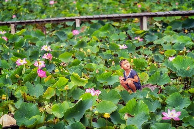 Het vietnamese jongen spelen met de roze lotusbloem over de traditionele houten boot in grote lak Premium Foto