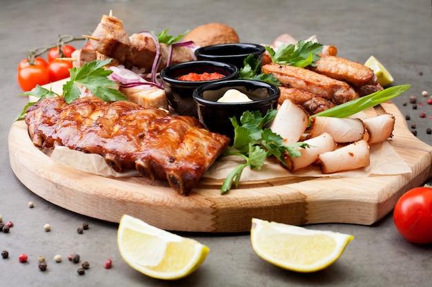 Het vleesbord is gevuld met bezuinigingen en steaks, versierd met kruiden, kerstomaatjes en citroenen. het concept van vlees of bier voorgerecht. Premium Foto