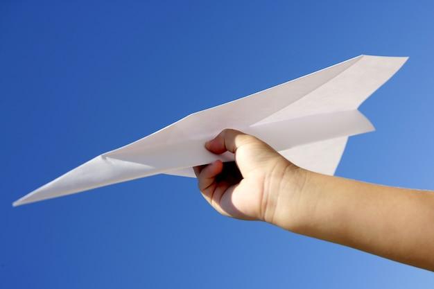 Het vliegtuig van het document in kinderen overhandigt blauwe hemel Premium Foto