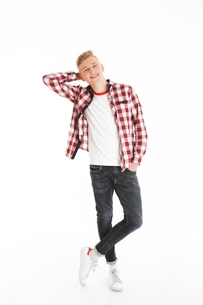 Het volledige lengteportret van modieuze hipsterjongen die plaidoverhemd dragen grijnzend en kijkend op camera houden dient zak in, geïsoleerd over witte muur Premium Foto