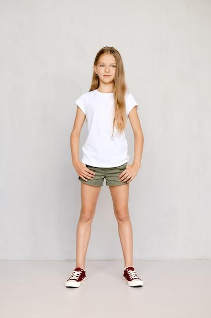Het volledige lengteportret van positief tienermeisje die zich rechtstreeks met beide bevinden dient zakken in Premium Foto
