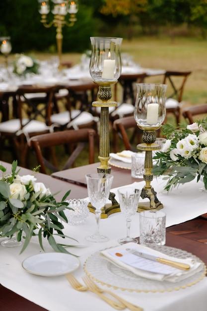 Het vooraanzicht van glaswerk en bestek diende in openlucht op de houten lijst met bloemensamenstellingen en kandelaars Gratis Foto