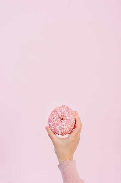 Het vooraanzicht van handholding verglaasde doughnut met bestrooit en exemplaarruimte Gratis Foto