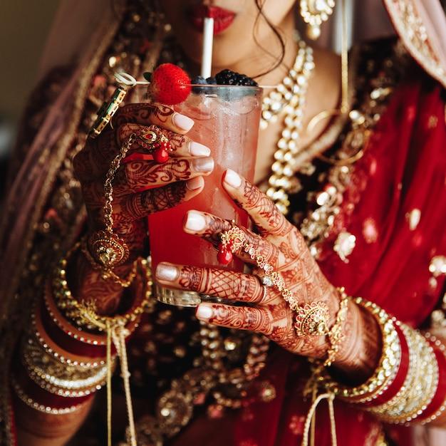 Het vooraanzicht van het gewas van indische bruid is drinkinkgcocktail in traditionele kledij Gratis Foto