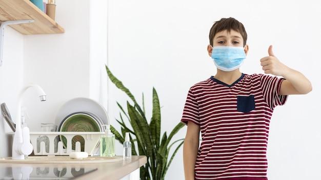 Het vooraanzicht van kind met het medische masker geven beduimelt omhoog Gratis Foto