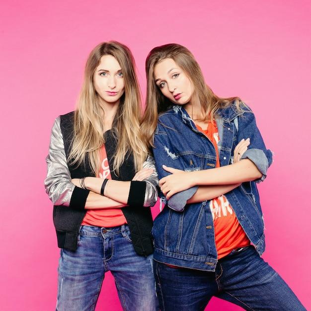 Het voorjaarsbeeld van twee positieve vrouwen met een bril, vrouwelijke vrienden met steil haar die knuffelen. een vrouw een spijkerjasje zet de horens van een vrouw. in alledaagse kleding en glazen. Premium Foto