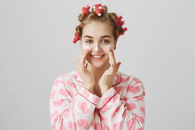 Het vrij jonge meisje in haarkrulspelden en pyjama past gezichtsroom toe Gratis Foto