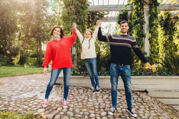 Het vrij jonge wijfje draagt rode sweater en jeans, houdt de knappe man hun kleine dochter met handen Premium Foto