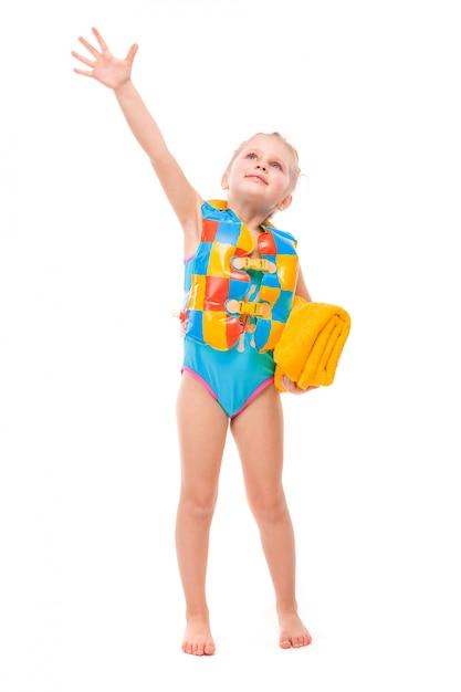 Het vrij leuke meisje binnen in blauw zwemmend kostuum en het kleurrijke reddingsvest houdt gele handdoek Premium Foto